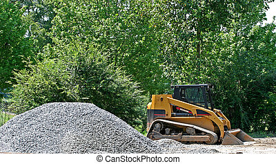 Working Gravel - A small bulldozer and a pile of gravel at a...