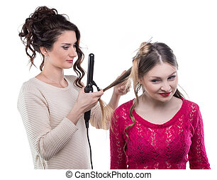 Working hairstylist curling client