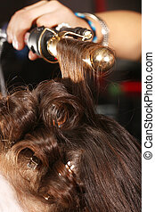 Working Hairstylist Curling Hair in a Salon