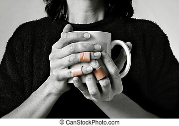 A women holding a coffee cup with bandaged fingers. The image is black and white and the bandages are natural color