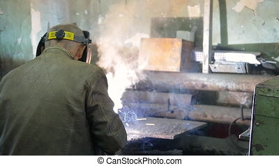 Working in a mask carries out welding of pipes in the manufactory
