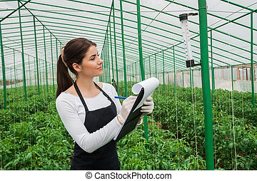 Working in greenhouse. Beautiful woman in uniform writing something in her note pad and looking at the thermometer while standing in greenhouse