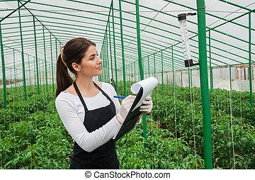 Working in greenhouse. Beautiful woman in uniform writing ...