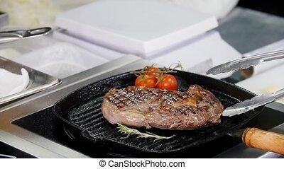 Working in the kitchen. Chef frying juicy piece of steak in...
