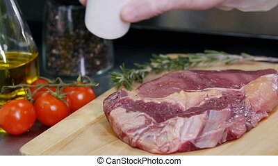 Working in the kitchen. Chef preparing the meat with salting...