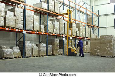 working in warehouse - worker in blue uniform in the...