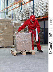 worker wrapping box on wooden pallet in warehouse