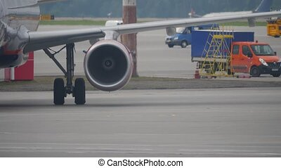 Working jet engine and landing gear of a jetliner moving on airport apron