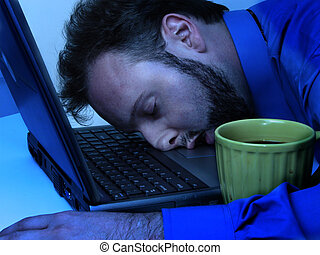 Working Late 1 - Man asleep on his laptop next to his...