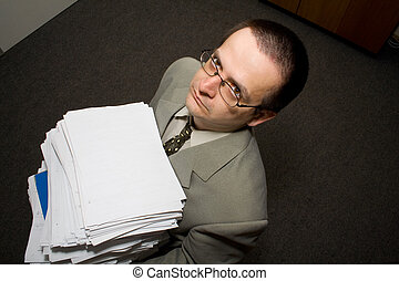 Working late in the office - Man working late with papers in...