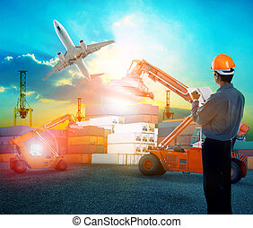 working man in logistic business working in container shipping yard with dusky sky and jet plane cargo flying above use for land to air transport and freight