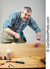 Working man - Senior man drilling plank in workshop