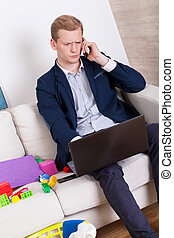 Working man talking on phone among child's toys