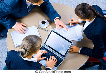Working meeting - Image of three business people working at...