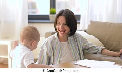 working mother playing with baby boy at home -...