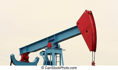 Working oil pump in a field on a bright background