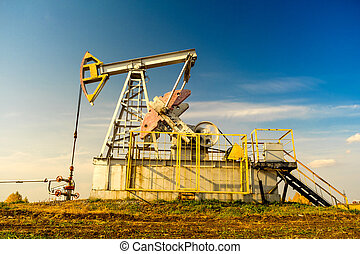 Oil rigs-rocking on the oil field near the road. Oil rig. Oil industry equipment.
