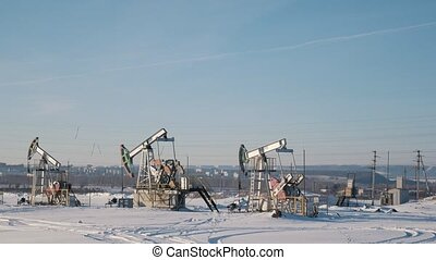Working oil pumps in the winter field on the background of the city