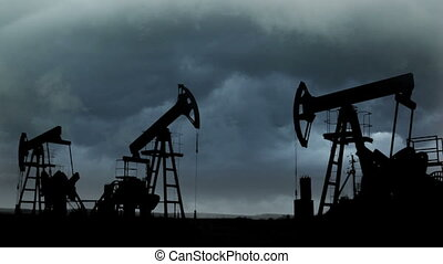 working oil pumps silhouette against the background of the dark storm clouds