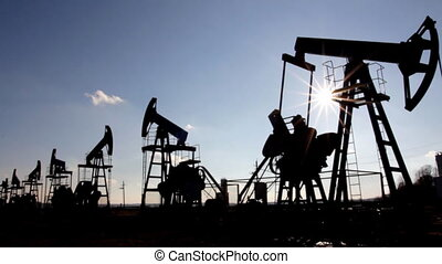 working oil pumps silhouette against sun - timelapse