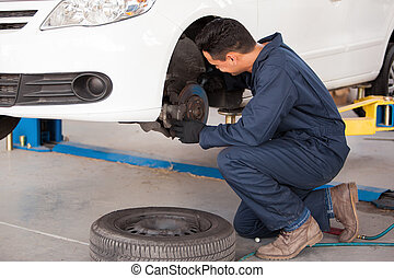 Working on a car brakes - Young mechanic fixing the brakes...