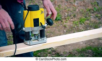 Working on a wooden plank with plunge router - Hands of man...