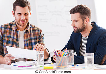 Working on creative project. Two confident business people in smart casual wear sitting together at the table and discussing something