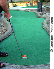 A man about to putt on a miniature golf course.