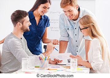 Working on project together. Four cheerful business people in smart casual wear discussing something while looking at the document together