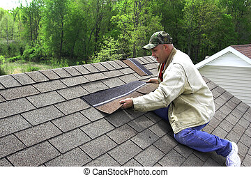 Roofer repairing damaged shingles after storm with very high winds came through over night