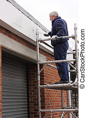 Working on scaffold tower - A painter working from a...
