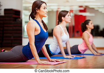 Working on the cobra yoga pose - Cute Hispanic women...