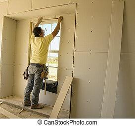 Sheetrock worker putting up sheetrock around the window frame