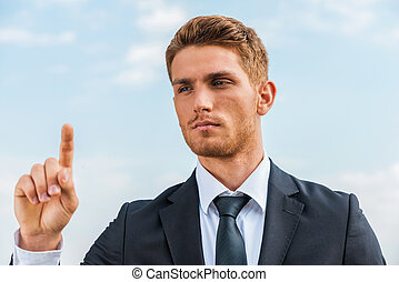 Working on transparent wipe board. Confident young man in formalwear touching a transparent wipe board while standing against sky background