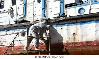 Working people tear off paint on metal in repairs process at shipyard.