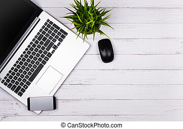 Working place on white wooden table with copy space. Laptop, mouse, phone, flower in a pot. Flat lay. Top view of blackboard office desk.