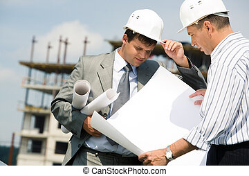 Portrait of confident businessmen with helmet working