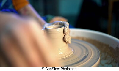 Working process of man's work at potters wheel in art...