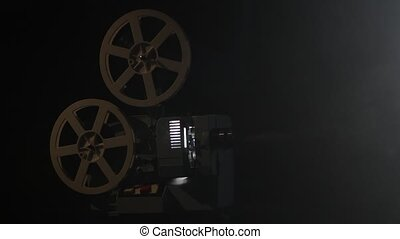 Working projector in the smoke. Black background studio