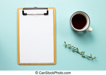 Working space. Clipboard and empty paper sheet with cup of coffee on blue background. top view