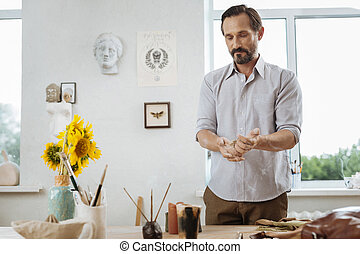 Dark-haired artist standing near his working table