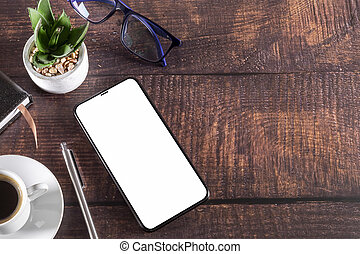 Working table with smartphone notepad coffee cup pen glasses plant on wooden
