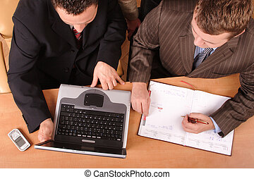 Two working business men planning - with laptop, calender, mobile phone on the desk