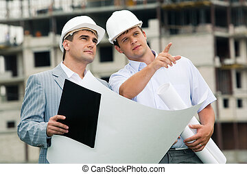 Working together - Photo of young engineer showing something...