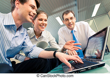 Portrait of confident business team sitting at the table and looking at laptop monitor in the office