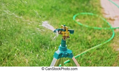 Working tripod garden sprinkler pan left in slow-motion -...