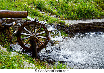 Working watermill wheel with falling waterin the village. -...