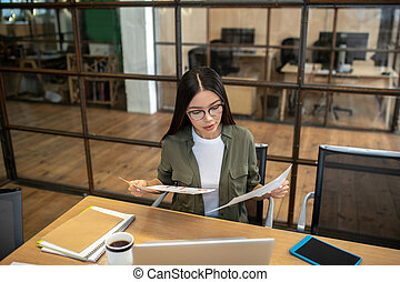 Long-haired brunette asian girl working in the office and looking concentrated