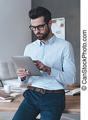 Working with his touchpad. Handsome young man wearing glasses and working with touchpad while leaning to the table in office