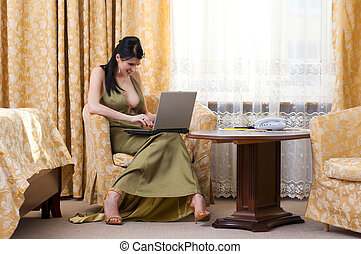 Beautiful woman in gown is sitting in the beautiful room and working with PC